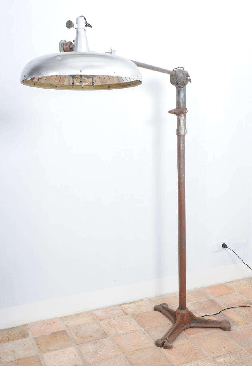 Antieke, industriële tandartsen lamp op oud gietijzeren statief
