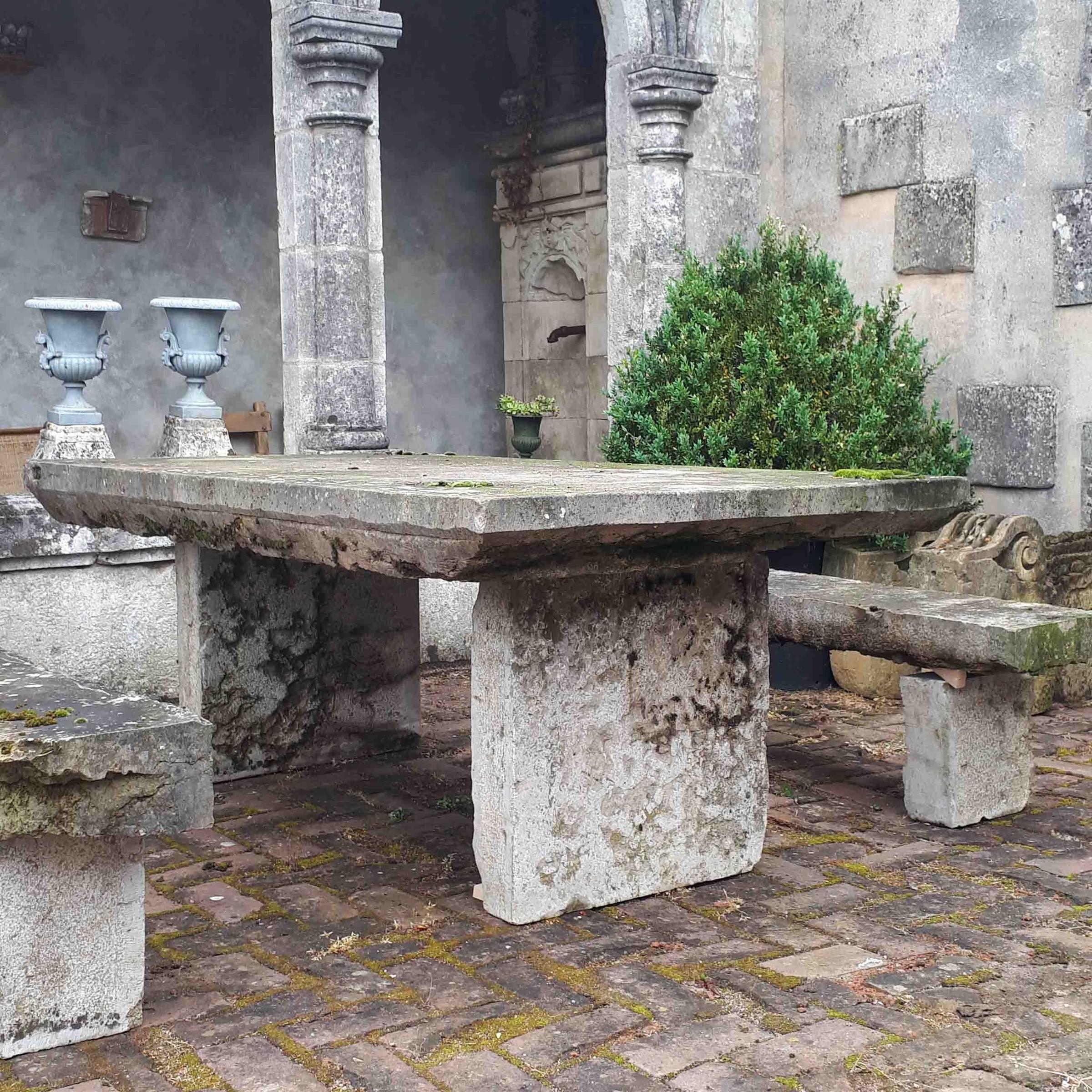 Oude natuurstenen tuintafel met bankjes