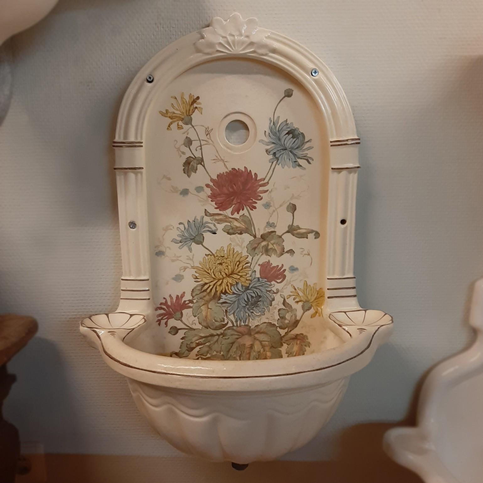 Oud wandfonteintje met coquilles en bloemmotief