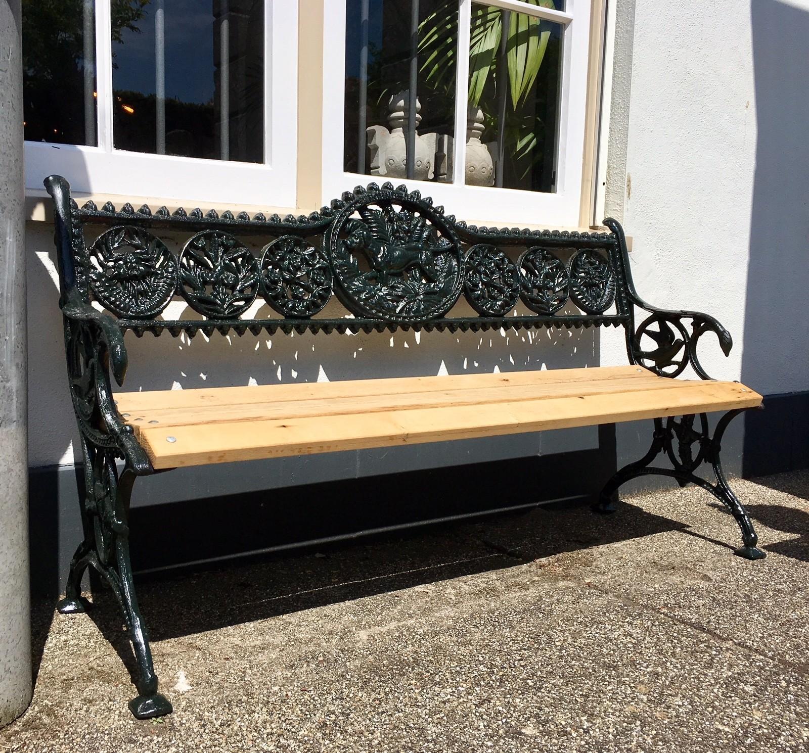 Oud decoratief gietijzeren tuinbankje met houten zitting